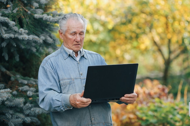 Elegant old man standing on gray background and using a laptop