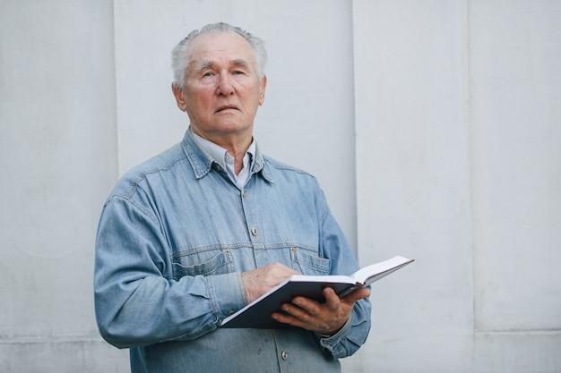 Uomo anziano elegante che sta sul fondo grigio con un libro