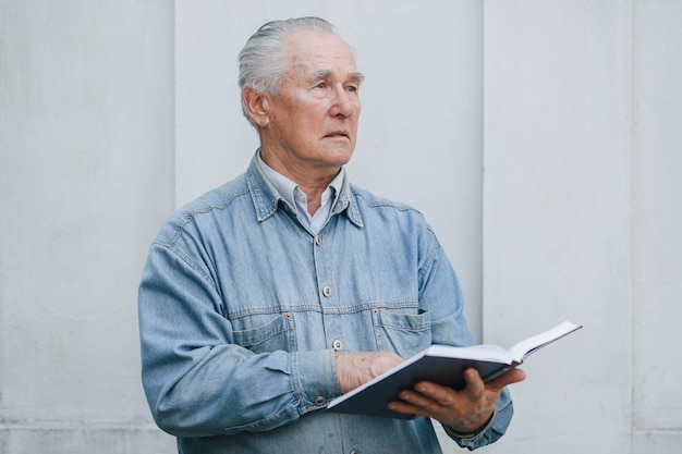 本を灰色の背景の上に立ってエレガントな老人