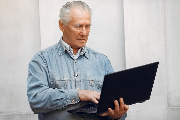 Elegant old man standing and using a laptop
