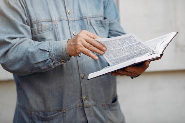 Elegante vecchio in piedi con un libro