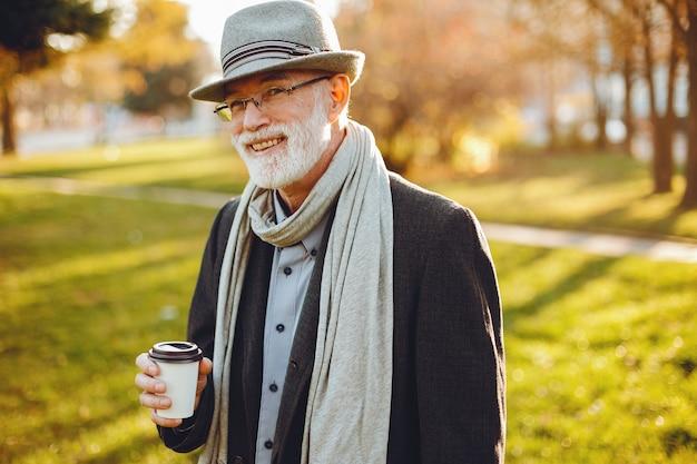Elegant old man in a sunny autumn park