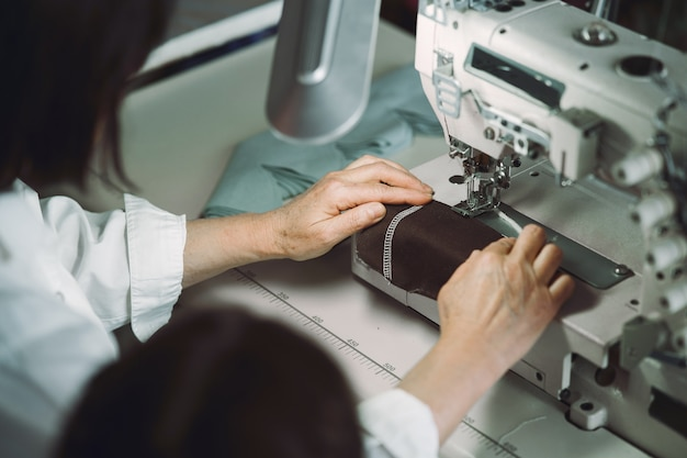 Шикарная старуха сидя в студии и шьет ткань