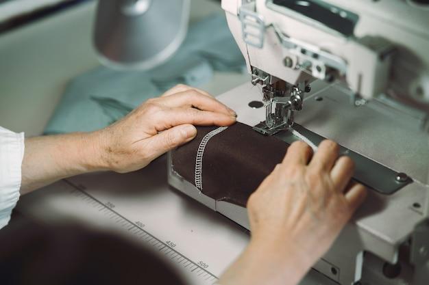 La donna anziana elegante che si siede nello studio e cuce il panno