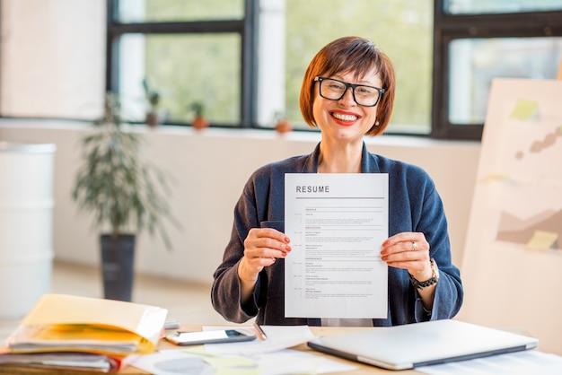Elegant older woman holding resume document sitting at the modern office