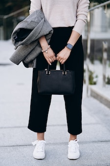 エレガントな服。織り目加工の大きな暗いバッグのクローズアップ。ストリートでポーズをとるモデル。短いズボン、クリーミーなセーター、グレーのコートまたはジャケット、白いスニーカーを着用しています。女性のファッションのコンセプトです。