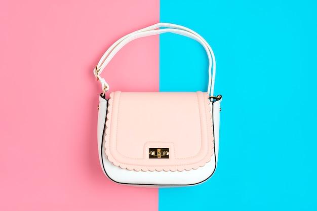 Элегантная пастельно-розовая, белая сумочка на цвет синий, розовая поверхность flat lay