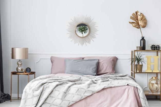 枕と毛布付きのベッドの上に太陽の形をした鏡が付いたエレガントなピンクとゴールドのベッドルームのインテリア