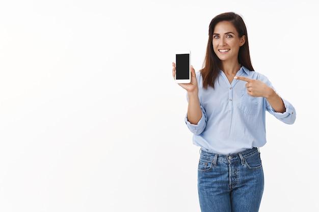 우아하고 잘 생긴 쾌활한 성인 여성이 스마트폰을 홍보하고, 휴대전화를 들고, 가제트 화면을 가리키며 앱 사용을 권장하고, 여름 휴가 사진을 보여주고, 행복하게 웃고 있습니다.