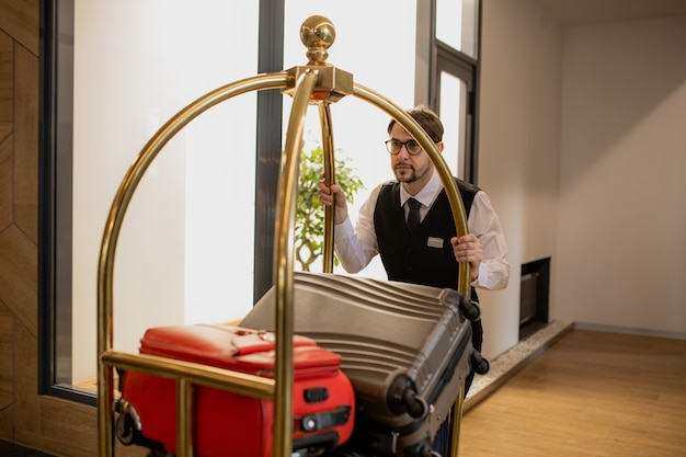 Elegant porter in eyeglasses pushing cart with pile of suitcases while moving along corridor inside hotel