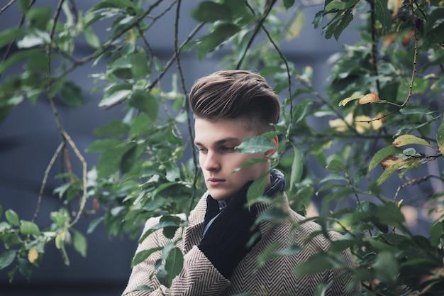 コートと秋の公園で手袋の男のエレガントな肖像画