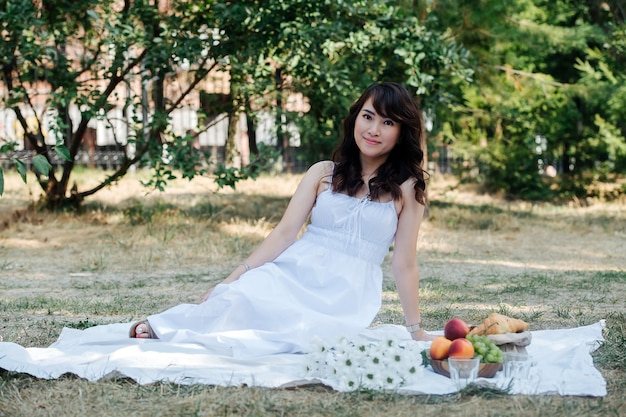 Elegant portrait of a uplifted lovely asian woman sitting on a blanket in a park. she's wearing white dress, having picnic in a park, enjoying last warm days of the early fall in tree shadow.