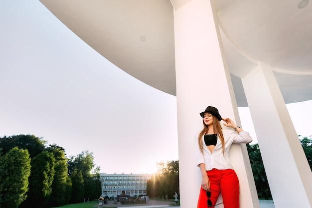 Элегантная поза молодой девушки, стоящей возле колонн и держащей в руке солнцезащитные очки