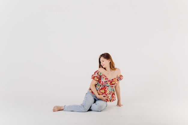 Elegant pregnant mom in dress posing in proud of her pregnancy