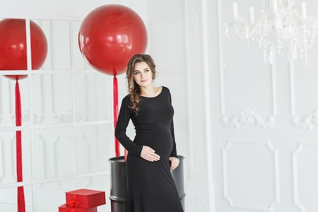 大きな赤い風船と黒のドレスでポーズをとってエレガントな妊婦