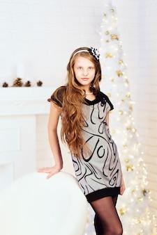 Элегантная длинноволосая улыбающаяся девочка-подросток в платье с елочными украшениями