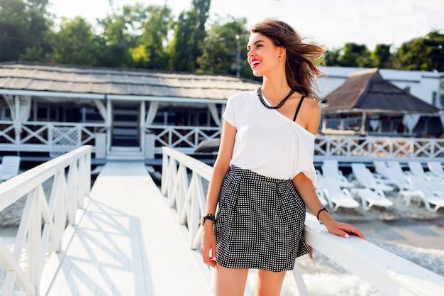 Donna abbastanza esile elegante in attrezzatura d'avanguardia di estate che posa vicino alla località di soggiorno di lusso vicino alla spiaggia. indossa una gonna alta elegante camicia e una t-shirt bianca.