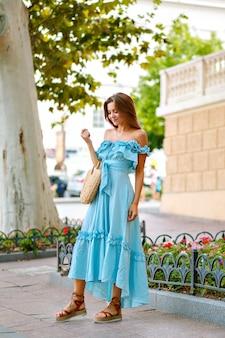Элегантная красивая женщина в модном модном синем макси-платье позирует в городском парке