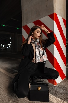 Elegant pretty young woman model in fashionable black clothes with vintage silk scarf with leather trendy handbag posing near striped pillar in city parking lot. european girl resting on the street.