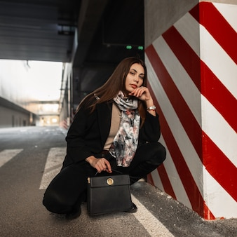 Elegant pretty young woman model in fashionable clothes with fashion silk scarf with leather black trendy handbag posing near striped pillar in city parking. cute girl rests on the street. beauty lady