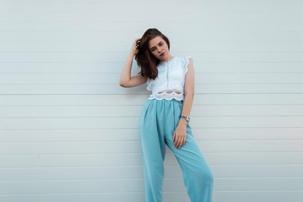 Элегантная симпатичная молодая женщина поправляет волосы. симпатичная девушка в модной кружевной блузке в винтажных синих штанах позирует