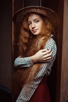 古い通路でポーズをとる麦わら帽子の長いウェーブのかかった髪を持つエレガントな赤毛モデル