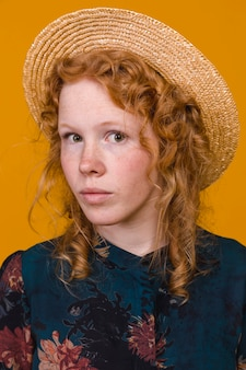 Elegant redheaded female in studio with colored background