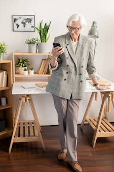 Elegant retired white-haired woman in grey suit texting in smartphone while standing by desk with working supplies