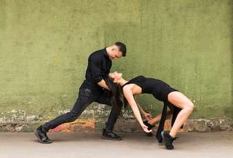 Elegant romantic couple dancing against old green wall