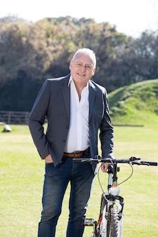 彼のバイクの隣にエレガントシニアビジネスマン