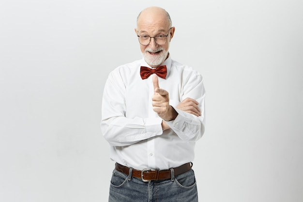 Elegant senior caucasian man with thick beard expressing positive emotions, pointing index finger  and laughing. unshaven elderly male wearing bow tie saying to you: good job