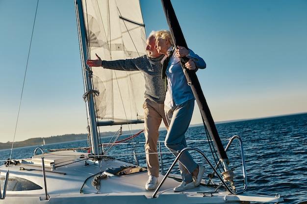 帆船の横に妻と立っている間、地平線を指している優雅な年配の男性