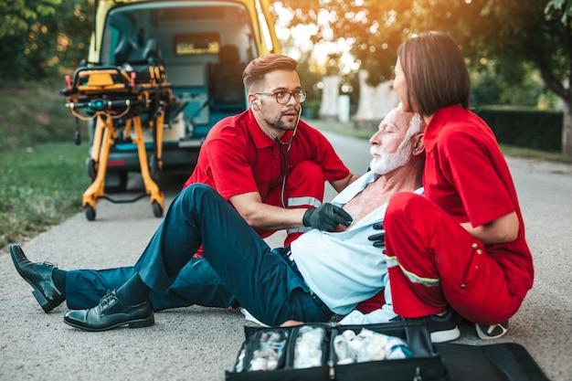 Элегантный старший мужчина с симптомами сердечного приступа сидит на дороге работников скорой медицинской помощи, пытаясь ему помочь. служба помощи водителю.