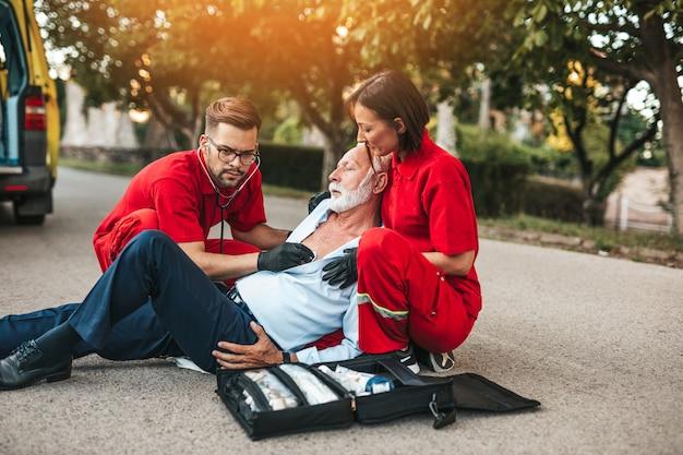 Элегантный старший мужчина с симптомами сердечного приступа сидит на дороге работников скорой медицинской помощи, пытаясь ему помочь.