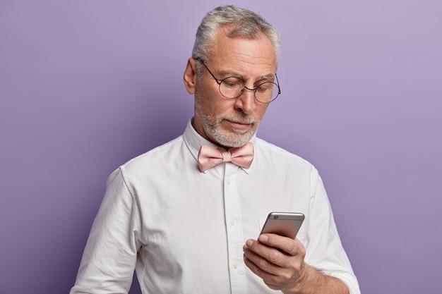 우아한 수석 남자가 자신의 휴대 전화에서 일하고 디스플레이에 집중하여 현대 기술을 사용하는 방법을 이해하려고합니다.