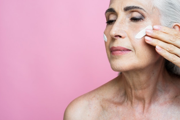 Elegant senior woman applying moisturizer