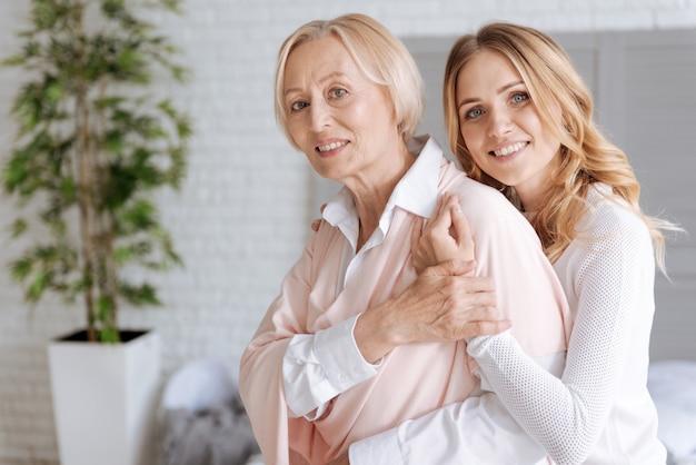 Элегантная старшая женщина закрывает руку дочери своей рукой, пока дочь обнимает ее сзади