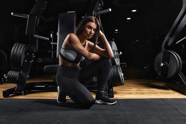 Элегантная чувственная брюнетка женщина позирует, сидя на полу в спортивном зале