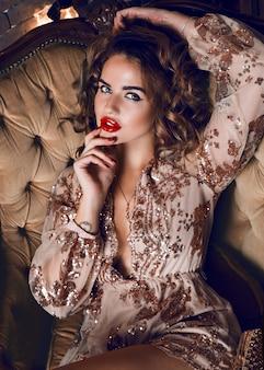 Элегантная чувственная женщина, сидящая в роскошном кресле