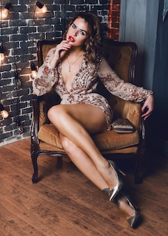 Elegant sensual woman sitting in luxurious armchair