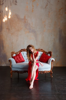 Elegant sensual young redhair woman in red dress sitting on classic sofa
