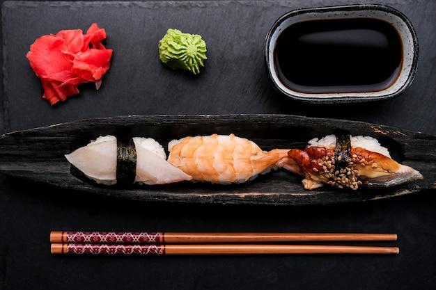 Элегантный сервированный набор суши со свежими креветками и сырым лососем на черной тарелке с имбирем был ...