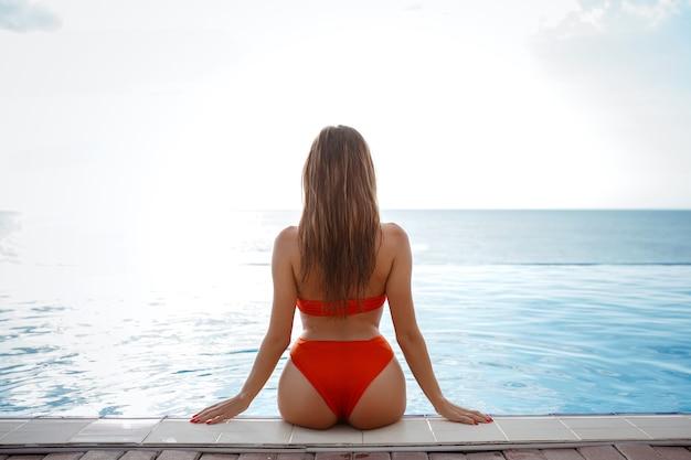 日焼けしたスリムで形の良い体にオレンジ色のビキニを着たエレガントでセクシーな女性がプールの近くでポーズをとっています。顔なし