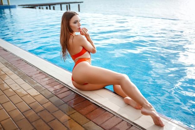 日焼けしたスリムで形の良い体のオレンジ色のビキニでエレガントなセクシーな女性がプールの近くでポーズをとっている