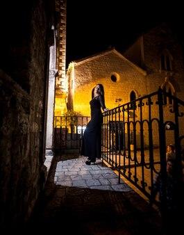 暗い古い通りでポーズをとってカクテル ドレスを着たエレガントなスリムな女性