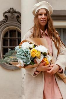 春に花束を持って屋外でエレガントな笑顔の女性