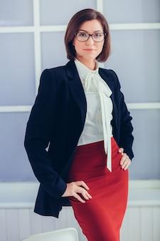 사무실에서 안경에 우아한 미소 비즈니스 여자.