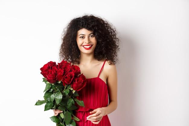 赤い唇とドレス、バラの花束を保持し、幸せそうな白い背景に見えるエレガントな笑顔の女性。