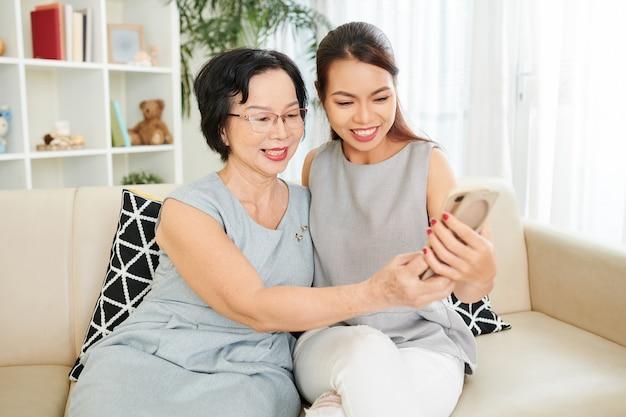 エレガントな笑顔の年配の女性と彼女の大人の娘が自宅のソファに座って自分撮りをしています
