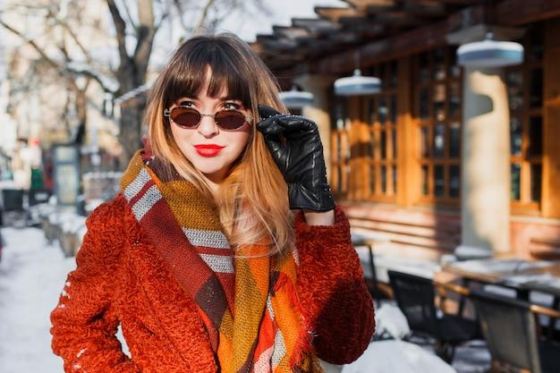 屋外ポーズレトロなメガネでエレガントな笑顔の女性